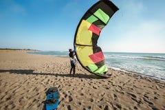 Yrkesm?ssigt surfareanseende f?r Caucasian man p? den sandiga stranden med hans drake och br?de royaltyfri foto