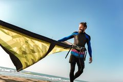 Yrkesm?ssigt surfareanseende f?r Caucasian man p? den sandiga stranden med hans drake arkivbild