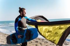 Yrkesm?ssigt surfareanseende f?r Caucasian man p? den sandiga stranden med hans drake royaltyfri foto