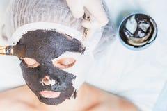 Yrkesmässig kvinna, cosmetologist i brunnsortsalongen som applicerar gyttjaframsidamaskeringen Arkivbild