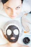 Yrkesmässig kvinna, cosmetologist i brunnsortsalongen som applicerar gyttjaframsidamaskeringen Royaltyfria Bilder