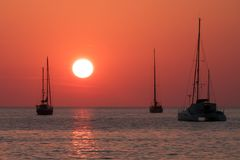 Yschts in the sea at sunset. Three yachts in the sea at red sunset stock images