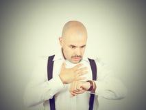 Łysi biznesmenów spojrzenia przy jego zegarek Fotografia Stock