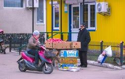 Žytomyr, Ucraina - 19 gennaio 2016: Il venditore suggerisce di comprare i frutti maturi Fotografie Stock Libere da Diritti