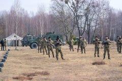 Žytomyr, Ucraina - 5 marzo 2015: I soldati ad una fermata puliscono le armi, riempiono le munizioni fotografia stock