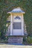 Ytterdörren med den härlig metallmarkisen - som är gammal och som är sliten men - uppsättningen i den täckte murgrönan vaggar hus arkivbilder