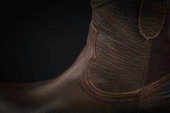 Ytterlighetnärbild av en brun lädercowboykänga på svart Arkivfoto
