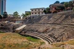 Yttersida av den forntida romerska amfiteatern med omgeende byggnader i staden av Durres Albanien royaltyfri foto