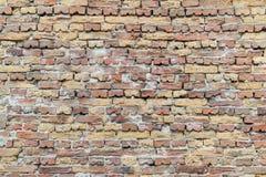 Yttersida av den gamla tegelstenväggen av röda och gula tegelstenar som förbinds med cementmortel royaltyfria foton