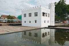 Yttersida av den vita historiska byggnaden reflekterade i vattnet av dammet i Kuching, Malaysia Arkivbild