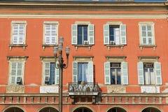 Yttersida av det härliga röda stuckaturhuset med traditionella franska slutarefönster i Nice, Frankrike Royaltyfri Foto