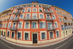 Yttersida av det härliga röda stuckaturhuset med traditionella franska slutarefönster och balkonger i Nice, Frankrike Arkivbilder