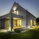 Yttersida av det upplysta huset bland gräsplan fotografering för bildbyråer