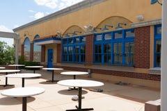 Yttersida av en byggnad med blåa fönster och en borggård arkivbild
