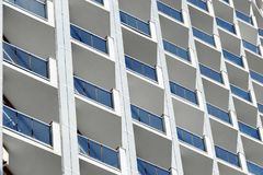 Yttersida av en skyskrapabyggnad med blåa fönster och konkreta delningar Industriell stads- bakgrund med att upprepa textur Royaltyfri Foto
