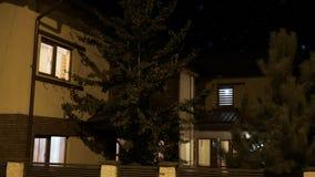 Yttersida av ett smart hus som är upplyst gradvist i varje rum i en bostads- grannskap på natten - stock video