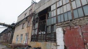 Yttersida av gammal övergiven industribyggnad med grungy fönster och väggar lager videofilmer