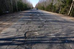 Yttersida av huvudvägen exponeras av de lutande strålarna av solen Stora gropar på vägen Ökande farafara dåligt royaltyfri foto
