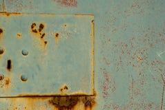 Yttersida av rostigt järn med kvarlevor av gammal målarfärgbakgrund arkivbild