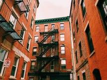 Yttersida för byggnader för lägenheter för Boston tegelsten röd med stegen för brandflykt arkivbild