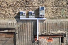 Yttre fördela av elektriska meter på en vägg Arkivfoto