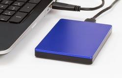 Yttre lagring förband till bärbara datorn vid usb-kabel på det vita skrivbordet Fotografering för Bildbyråer