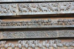 Yttre vägg för Hoysaleswara tempel som snider visa dragkampen och mystiska djur Arkivbild