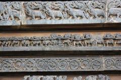 Yttre vägg för Hoysaleswara tempel som snider visa dragkampen och mystiska djur Royaltyfri Bild
