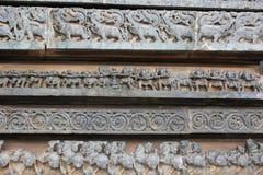 Yttre vägg för Hoysaleswara tempel som snider visa dragkampen och mystiska djur Royaltyfria Foton