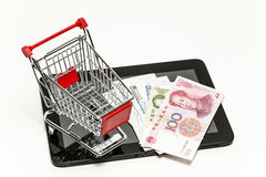 Yuan banknots, tablet computer and shopping cart. Symbol photo Royalty Free Stock Photography