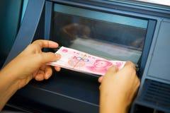 Yuan cinesi che pubblicano dal BANCOMAT a disposizione Fotografia Stock