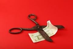 Yuan cinesi del taglio di forbici sopra fondo rosso Fotografia Stock Libera da Diritti