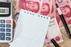 100 yuan con il calcolatore ed il blocco note Fotografia Stock