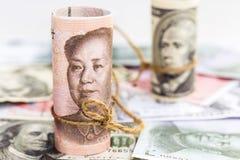 Yuan de China contra cédula do dólar americano em uma pilha da proibição das moedas Fotografia de Stock Royalty Free