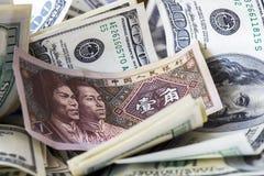Yuan entre billetes de dólar Imágenes de archivo libres de regalías