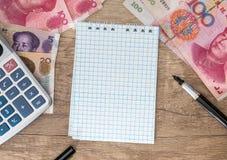 100 yuan med räknemaskinen och notepaden Arkivbild