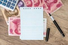 100 yuan med räknemaskinen och notepaden, Arkivfoto