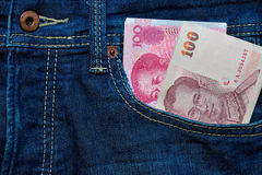 Yuan or RMB and Thai Baht in Jean's pocket Stock Image