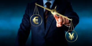 Yuan Sign Outweighing The Euro en una escala de oro Foto de archivo libre de regalías