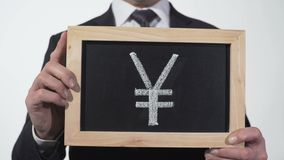 Yuan symbol drawn on blackboard in businessman hands, Chinese currency, Asia. Stock footage stock footage