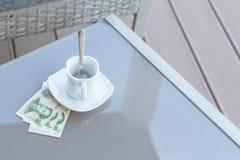 Yuans chinois et tasse de café vide sur une table en verre de café extérieur Paiement, astuce image libre de droits
