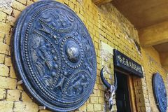 Giant bronze shield and goats head decorates the facade of house in Yuanyang stock photography