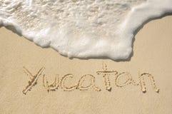 Yucatan geschrieben in Sand auf Strand Stockbilder