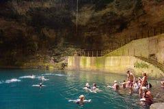 Dark cenote (water reservoir) underground in Yucatan, Mexico. YUCATAN, MEXICO - NOV 4, 2016: Unidentified people  swim in the Dark cenote (water reservoir) Stock Image