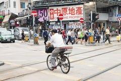 Yuen Long Hong Kong- Oktober 7, 2016: Folk som på fötter och på korsar vägen och stången cykeln på den Yuen Long drevstationen Arkivbilder