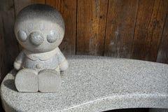 Yufuin,日本- 2017年5月13日:Anpanman,普遍的芳香树脂字符,花岗岩石雕塑坐沿公开路的长凳 免版税库存照片