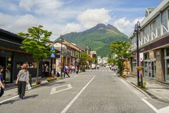 Main road from train station filled with people, streetscape and local shops direct to fresh green Yufudake mountain peak and blue. Yufuin, Japan - May 13, 2017 Royalty Free Stock Photos