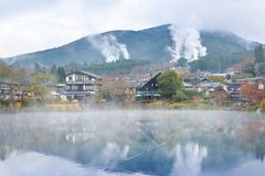 Yufuin town with hot spring smoke, Japan. Yufuin town with hot spring smoke is seen from the other side of Lake Kinrin, Yufuin, Japan stock photo