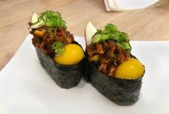 Yukke o sushi del maki de Gunkan que remata con carne de vaca picadita picante y yema de huevo cruda de codornices imagen de archivo