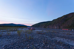 Yukon midsummer night tent camp and beached canoes Royalty Free Stock Images